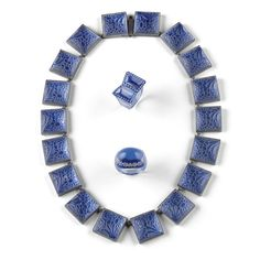 RENÉ LALIQUE  `FLEURETTES': A NECKLACE, (MARCILHAC NO. 1506) composed of eighteen square panels, each moulded with flowers and backed with lavender blue foil and within silver coloured metal mounts  metal stamped, `LALIQUE'  45cm.;  17 3/4 in.  designed 1922
