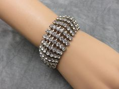 Fashioned in beautiful rows of sparkling rhinestones, this handsome bracelet is vintage art deco to finish your flawless runway look; even if your runway is the red carpet at work.