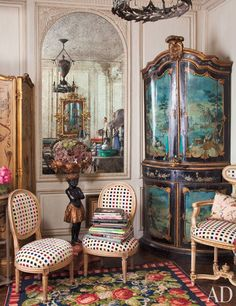 The entry contains an 18th-century French screen (left), an early-18th-century painted Genoese corner cabinet, and Louis XVI–style chairs upholstered in an Old World Weavers cut velvet. The needlepoint carpet is English | archdigest.com