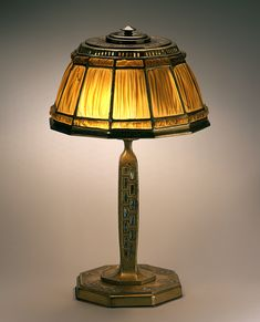 Reading lamp, c. 1915. Shade No. 1928, Favrile-Fabrique glass, Abalone desk set; Standard No. 604, inlaid abalone, gold finish; molded glass, bronze, abalone shell; Tiffany Studios, New York, 1902–32; H. 16 1/2 in. diam. 10 in. (68-003:17).