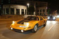 Während sich die Sonne verzieht, der Asphalt noch flimmert, leisten die Klappscheinwerfer des Mercedes C 111 den Lichtern der Großstadt Gesellschaft. Ausfahrt mit dem legendären Experimentalauto.