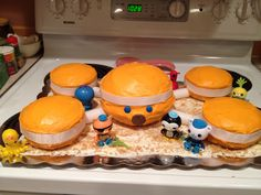 "Octonauts cake using Pyrex (and small fiestaware bowls), orange frosting, white fondant strips, set on a white frosting and graham cracker ""sand"" base. Little bits of sour strips for kelp and purchased figurines."