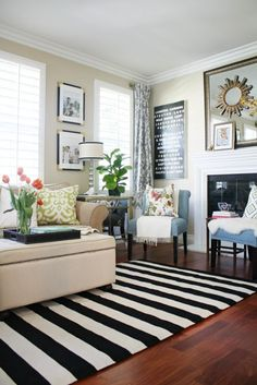 from A Thoughtful Place.  Black and white striped rug.  Black accents on wall.  Pops of color in living room.