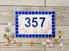 This outdoor house number, made of ceramic tiles in Iridescent Ultramarine Blue with real seashells, is generous in size so it can be easily seen from the road. This design best suits 3 or 4 digit house numbers. Perfect for your beach house or just to remind you of that special holiday. Mount it at the front door or on the mailbox.  Made to last with 75mm ceramic tile numbers surrounded by real shells embedded in the design. This tile, measures approx. 30cm x 20cm (12 x 8).  All my mosaics…