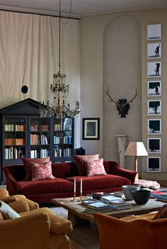 Love the grouping of velvet sofas in varying shades of crimson, saffron and…