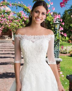 Look like a princess in this beaded Venice lace ball gown featuring an included off the shoulder popover jacket, sweetheart neckline, dropped waistline, and chapel length train. Jacket also available separately as style 3928J.