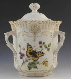 This is an amazing porcelain biscuit barrel made by Tressemanes and Vogt of Limoges, France between the years of 1892 to 1907. This gorgeous piece is hand painted with butterflies, moths, bees, and flowers with gold highlights.