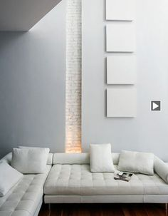 trevortondro Warming and beautiful feature: Lighted vertical strip of brick painted white between white  walls with mounted white squares.