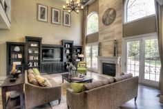 two story great room with windows/doors beside fireplace and entertainment wall