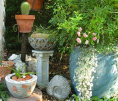 A collection of objects and pots next to 'La Marne' in the light blue pot. The object holding the pot with cactus is an upside down lamp stand