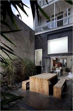 moderne stadstuin met strakke beton terras en houten teak meubelen