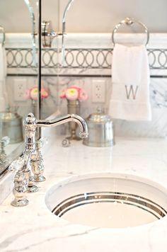 bathrooms - marble vanity top round sink marble tiles backsplash marble inset tiles monogrammed towel Glam bathroom with marble countertop,