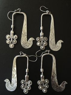 China | Earrings from the south China hilltribe. These are traditionally worn with the whole piece going through the earlobe like a weight ~ these one have however been modified in that an additional ear hook has been added so that they can be worn with regular pierced ears. © Jose M Pery.