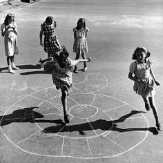 Girls playing hopscotch...when children actually played games on the playground
