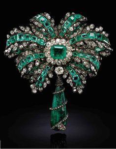 Emerald, ruby and diamond brooch, 19th century. Of ribbon bow design, the centre set with a step-cut emerald within a border of cushion-shaped and rose diamonds, surrounded by similarly set ribbon motifs, suspending a detachable emerald drop, encircled by a serpent set with rose diamonds and cabochon ruby eyes. French assay marks.
