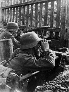 1941, Union Soviétique, Un soldat allemand armé d'un fusil antichar PZB-39 (Panzerbüchse 39) de 7.92mm surveille le front depuis sa tranchée. Un soldat en arrière-plan, armé d'un Mauser 98k. |