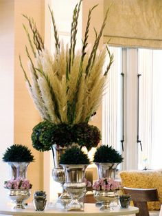 Plumes of pampas grass with gladiolus in a tall vase. Gives the illusion of feathers.