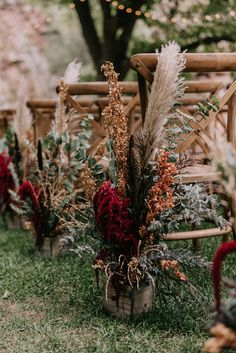 Boho-inspired floral aisle markers with pampas grass, greenery, and pops of red | Image by June Cochran Photography
