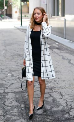 Street style look com vestido preto, choker e maxi casaco.