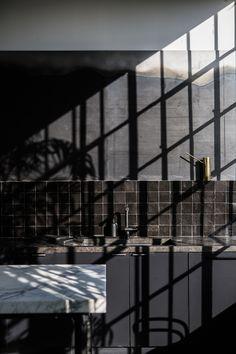 Black kitchen with tile and steel backsplash with dappled light