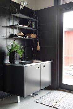 Pukutilan nurkkaus on kaakeloitu samalla Pukkilan mustalla Via Emilia Nero- laatalla kuin keittiön ja suihkutilan seinät. Topi-keittiöiden Lato-kaapisto on saanut pintaansa tumman sävyn. Kaapiston päällä Zarrosta hankittu Ox Denmarq Morse -seinähylly.
