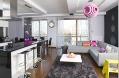 Aranżacja kuchni jest nowoczesna i kontrastowa. Projekt kuchni z wyspą uwzględniał połączenie jej z salonem. Białe meble kuchenne ciekawie prezentują się na tle ciemnych ścian i blatów. Ściany w kuchni pokryto tapetami i zabezpieczono szkłem.