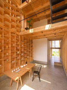 with a limited budget and a constricting plot of land, the home has been designed as a single, continuous space with a shelving system running the full height of the interior.