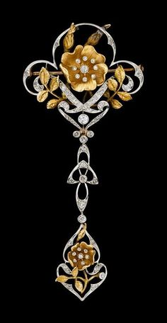 Art Nouveau platinum and yellow gold diamond garland brooch. Yellow gold blooming rose, platinum and diamond 'pistils'. Diamond set platinum ribbon drop finishing in petite yellow gold blossom.