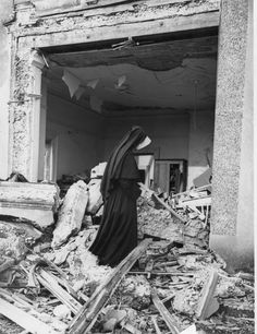 A nun at a convent school in the home counties inspects the damage done to one of the classrooms after a Nazi bomb hit the school during a night raid in London, March 21, 1941. Five nuns were injured during the bombing. (AP Photo)