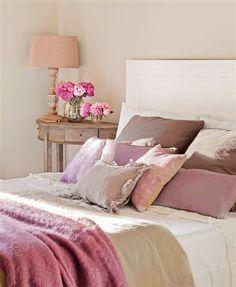 Detalle de cama con cojines y ropa de cama en tonos malva