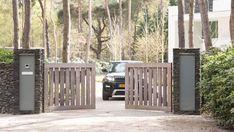 Padoek houten draaipoort (wooden gate padouk). In Lieshout heeft Preza poorten deze elektrisch bediende draaipoort met looppoort met leistenen pilaren geplaatst.