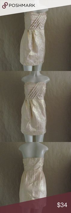 """Urban Outfitters Kimchi Blue Strapless Dress In great pre-owned condition Urban Outfitters strapless cocktail dress. Size 4. It's a shimmery iridescent gold, the color is best shown in the 4th photo. Has a sweetheart neckline with a pleated top and waist. Has a back hidden zipper and hook closure. There is a tiny hole near the left armpit, please see the last photo. Measurements: 16"""" underarm to underarm, 14"""" waist, 26"""" length. No trades. Open to reasonable offers. Happy Poshing! Urban…"""