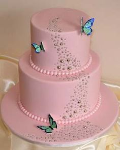 Small two tier pastel pink fondant wedding cake decorated with blue/green butterflies
