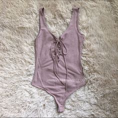 Rose Blush Lace Up Scoop Back Bodysuit A bodysuit in the prettiest shade of Rose! Features a lace up front, scoop back, and hook and eye closure. Ribbed material.  97% Rayon 3% Spandex Hand wash cold Tops Tank Tops