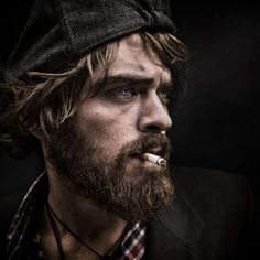 A bearded man in a checked shirt poses with a cigarette in his mouth Lee Jeffries