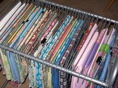 Fabric Organized - DIY - make with plastic boxes that fit cupboard (router indents from top edges) and use bottoms of plastic hangers to hang fabric. ===alternate idea, using file folders that hang inside drawers, drape fabrics over the folders to organize. smaller scraps could go inside the folder itself