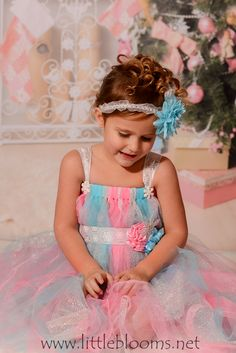 The Snowflake Tutu Gown has the best color combination: yummy pink, soft baby blue & sparkling silver. And it gets even better. It is interlaced with delicate silver edged lace and dainty sheer pink ribbons. A shimmering snowflake sash gathers the gown. The sash is adorned with a flower cluster of soft pink, baby blue and a glittery silver snowflake.