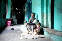 SPITI VALLEY, Man sitting with his granddaughter and smoking Hukka in his house in Rakchham Village, Sangla, Himachal Pradesh, India