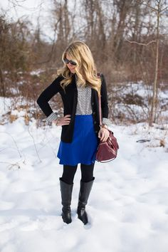 A classic black and white blouse is paired with a blue flared skirt and tights for a winter office look...click through for more what to wear to work outfit ideas!
