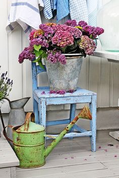 flowers, watering cans and an old chair for country charm