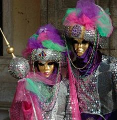 2 People With Gold Mask & Purple,Pink,Green & Greyish Black Costumes