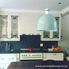 Country style kitchen with mint pendant light.