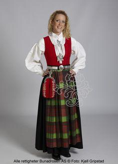 Nordmørsbunad med rødt liv, sort stakk, rutete forkle i skarpe farger, skjorte med labbsøm og tett sølvbelte.