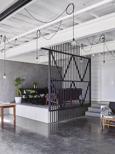 White walls, grey wall, grey floors, white ceiling, black gate, dark grey couch, and hanging lights