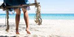 Woman sitting on a wooden swing on the beach - Perfect summer view.