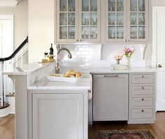 pale blue paint in glass cabinets, paneled dishwasher, corbels under upper cabinets, pale gray cabinets