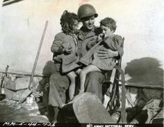 American artillery-man PFC Evane Sheldon of Bothell, Washington, enjoys watching two small Italian children on his lap eating his candy. Anzio, Italy. 30 January 1944. U.S. Army Signal Corps photograph, from the collection of The National World War II Museum