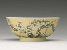 A CAFE-AU-LAIT-GROUND FAMILLE-VERTE BOWL QING DYNASTY, KANGXI PERIOD the exterior neatly painted with an aubergine-glazed knotted and twisting prunus tree issuing bountiful branches and blossoms with a pair of birds in between, all against an evenly toned cafe-au-lait ground, the interior and base glazed white, apocryphal six-character Xuande within a double circle