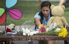 BOSTON, MA - AUGUST 12: Mariagrazia LaFauci of Waltham, Massachusetts places a teddy bear on a fan memorial in honor of Robin Williams on the bench made famous by his movie 'Good Will Hunting' in Boston Public Garden on August 12, 2014 in Boston, Massachusetts. Williams died after hanging himself on August 11, 2014 at his home in Tiburon, California. (Photo by Michael J. Ivins/Getty Images)