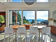 Floor-to-ceiling windows provide a spectacular view while seated in this luxury dining room.